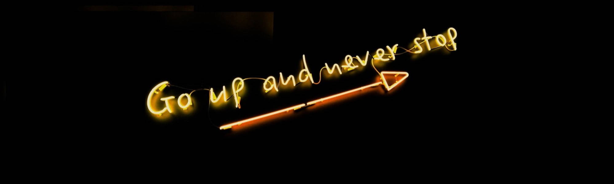 Neon light saying go up and never stop